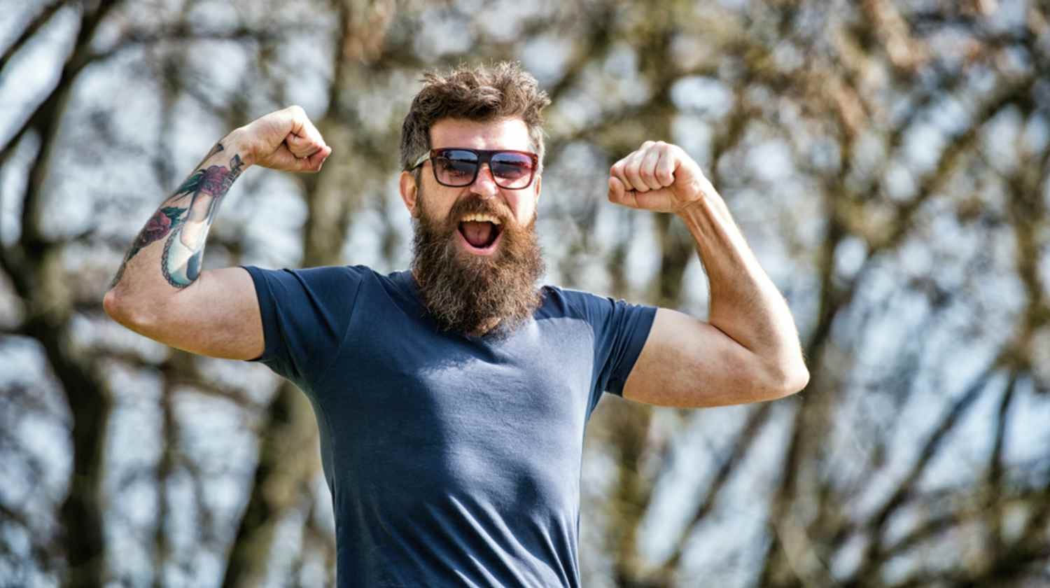 Feature | Bearded man showing his biceps | Tips For Growing A Long Beard