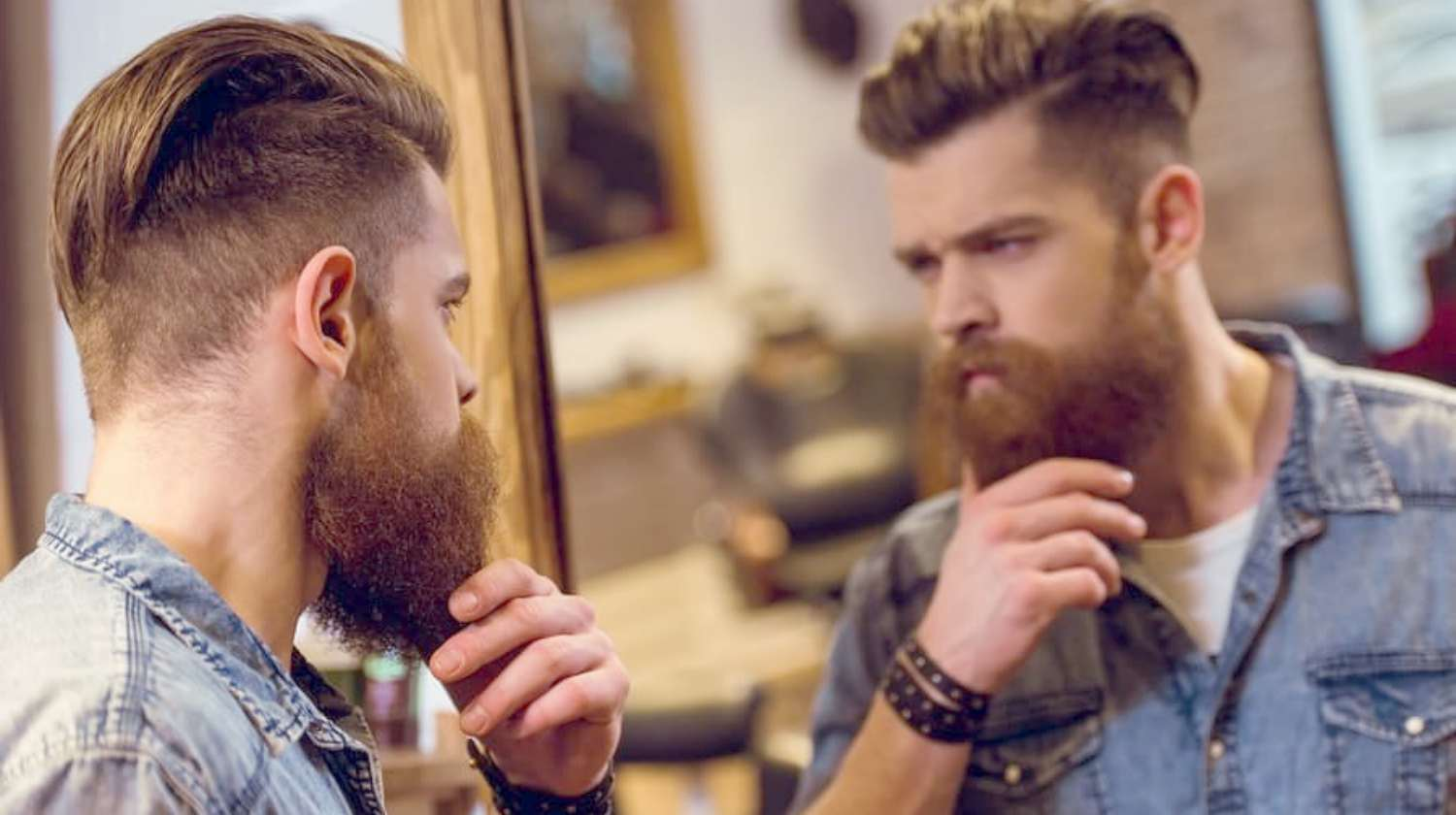 Feature | bearded man looking at the mirror | Beard Hacks You Have To Know | beard hacks
