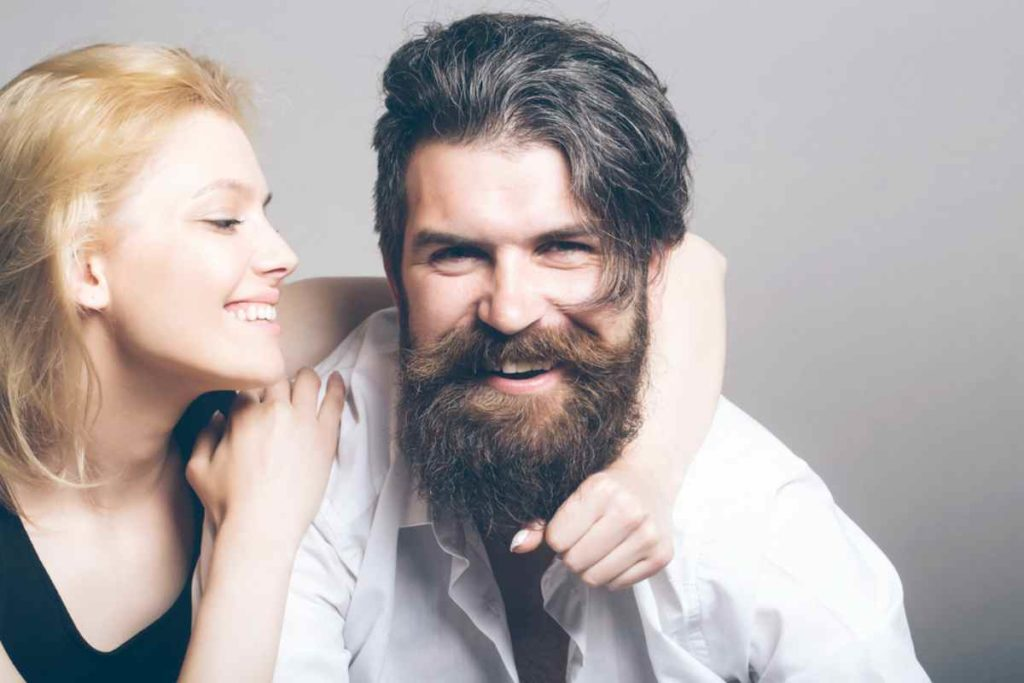 Beautiful woman holding man's beard | Tips For Growing A Long Beard