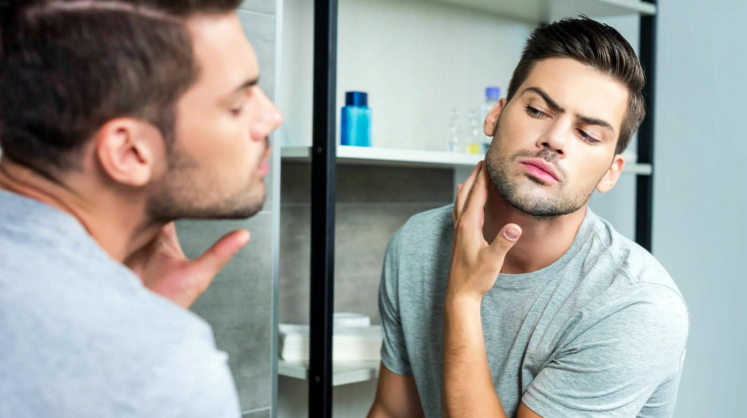 Feature | young man looking mirror checking his bristle | How To Get Rid Of Beard Rash Once And For All | skin rash